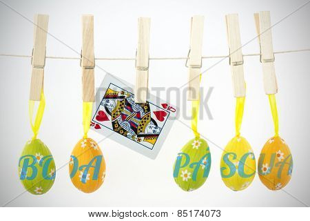 boa pascua against easter eggs hanging from a line with queen of hearts