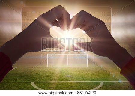 Woman making heart shape with hands against football pitch with goalpost and scoreboard