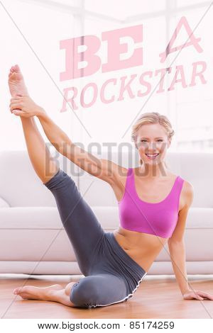 Athletic blonde sitting on floor stretching leg up smiling at camera against be a rockstar