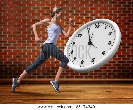 Pretty fit blonde jogging against room with brick wall
