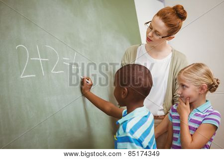 Side view of teacher assisting little boy to write on blackboard in the classroom