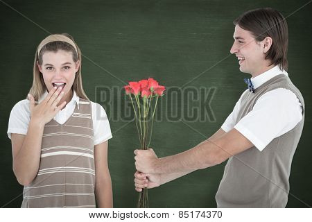 Geeky hipster offering red roses to his girlfriend against green chalkboard