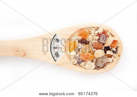 weighing scales against wooden spoon with muesli
