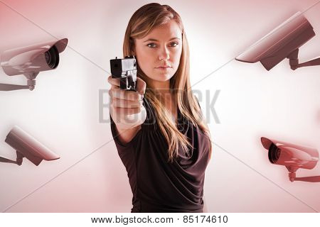 Femme fatale pointing gun at camera against cctv camera