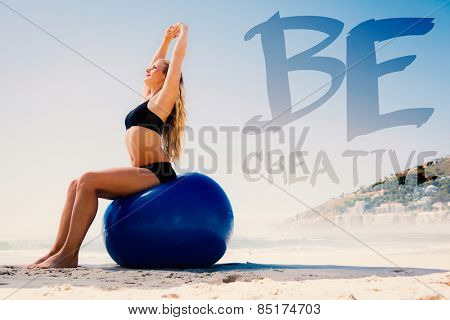 Fit blonde sitting on exercise ball at the beach against be creative