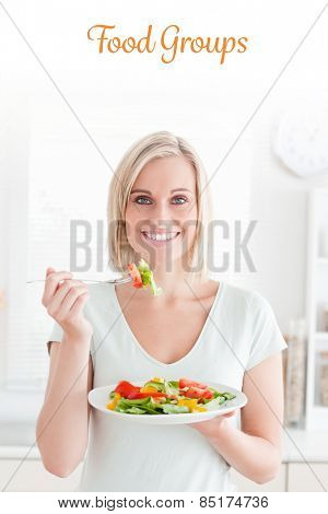 The word food groups against portrait of a blonde woman eating mixed salad