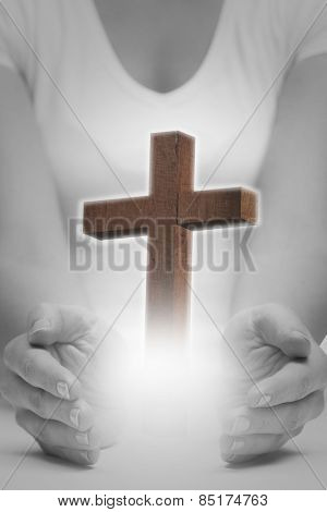 Hands presenting against wooden cross