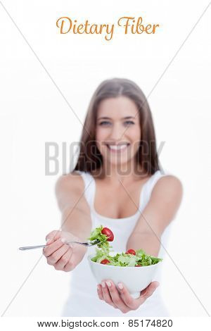 The word dietary fiber against delicious salad being eaten by a young woman