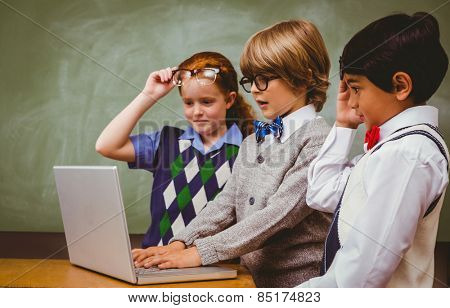 Little school kids using laptop in the classroom