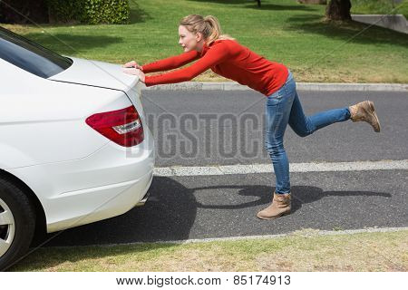 Young woman pushing her broken down car in the street