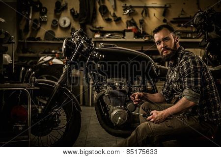 Mechanic building vintage style cafe-racer motorcycle  in custom garage