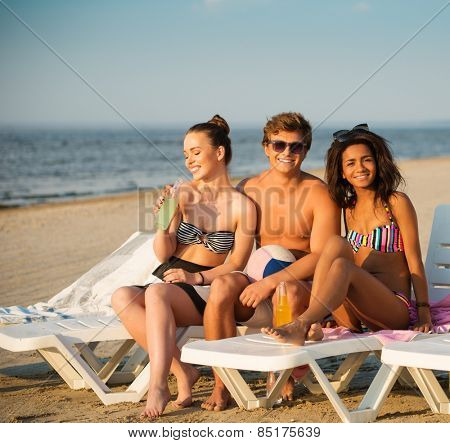 Group of multi ethnic friends sunbathing on a deck chairs on a beach