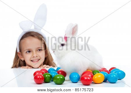 Happy little girl with her easter bunny - smiling and enjoying the magic, isolated