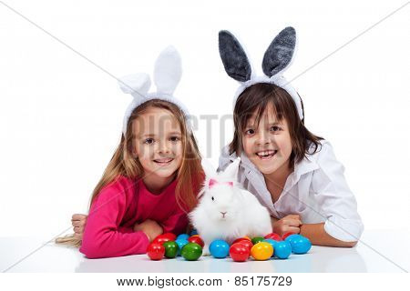 Happy kids with the easter bunny and colorful eggs - wearing bunny ears