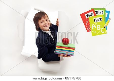 Back to school concept - boy with books looking through hole in billboard