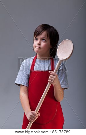 What should I cook today - young chef boy with large wooden spoon