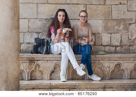 DUBROVNIK, CROATIA - MAY 28, 2014: Young girls eating pizza cut in front of Rector's Palace.
