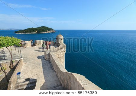 DUBROVNIK, CROATIA - MAY 26, 2014: Tourist at Old city walls with Lokrum island and Adriatic sea in background. Old wall is one of Dubrovnik's most famous feature. It is almost 2 km long.