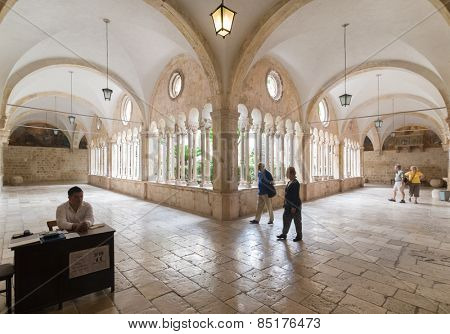 DUBROVNIK, CROATIA - MAY 26, 2014: Tourists in hallway around famous courtyard in Monastery of the Friars minor. It is the most important work from transitional period from Romanesque to Gothic style