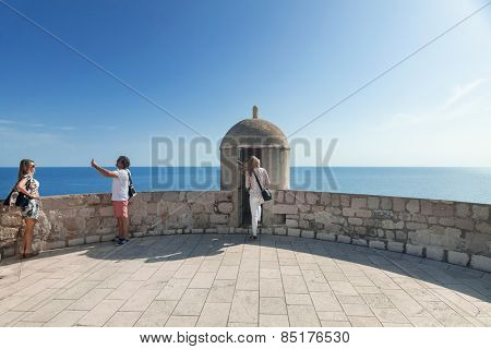 DUBROVNIK, CROATIA - MAY 26, 2014: Tourist taking photos at Old city walls with Adriatic sea in background. Old wall is one of Dubrovnik's most famous feature. It is almost 2 km long.