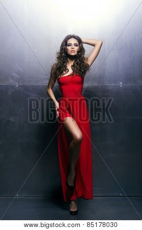 Young, beautiful and passionate woman in a wavy, long, red dress over an iron background