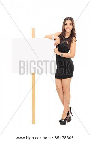 Full length portrait of an attractive woman standing next to blank signboard isolated on white background