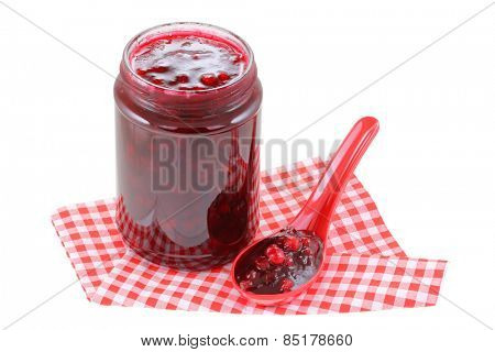 A spoon next to a jar of Cranberry jam isolated on white background