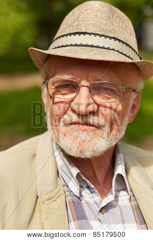 Pensive old man with hat and glasses sitting in a park in fall