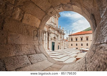 DUBROVNIK, CROATIA - MAY 26, 2014: View on The Assumption Cathedral entrance through circular stone opening. Cathedral is the seat of the Roman Catholic Diocese of Dubrovnik.