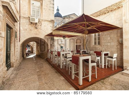 DUBROVNIK, CROATIA - MAY 26, 2014: Empty restaurant terrace in the street passage. Dubrovnik has many restaurants which offer traditional Dalmatian cuisine and some great wine lists.
