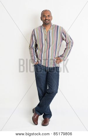 Full length confident Indian guy in casual wear standing on plain background with shadow.