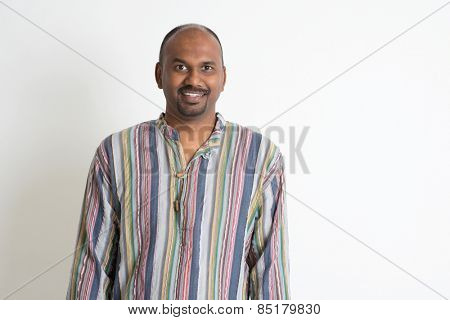 Portrait of smiling Indian man on plain background with shadow