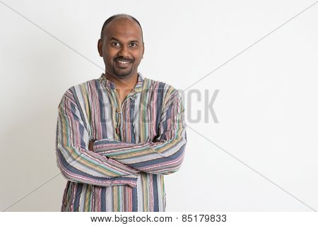 Portrait of smiling Indian man arms crossed on plain background with shadow