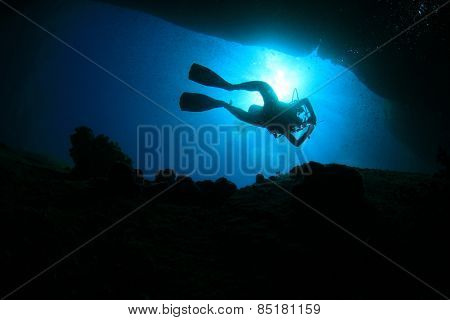 Scuba diver silhouette swimming through underwater canyon