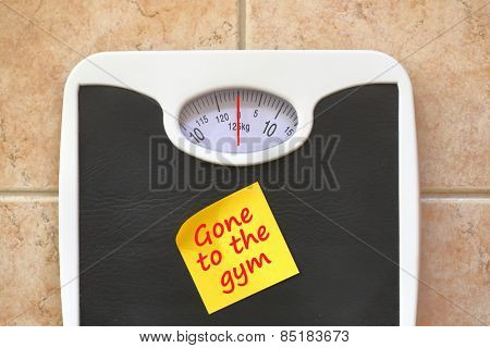 Bathroom scale with Go to Gym memo sticker. Diet and fitness concept