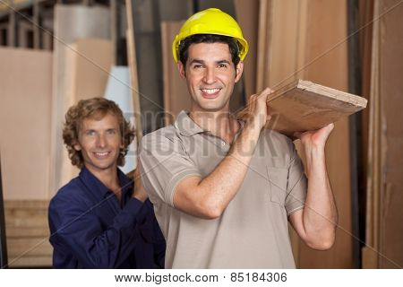 Portrait of happy carpenters carrying wooden plank together in workshop