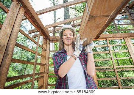 Portrait of confident female worker carrying wooden planks at construction site