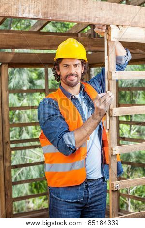 Portrait of confident male worker measuring timber frame with tape at construction site