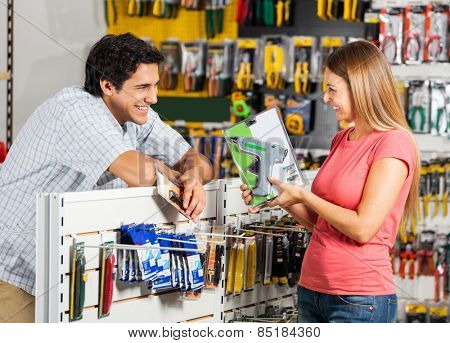 Playful couple with cordless drill in hardware store