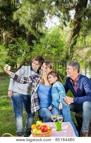 Smiling family taking selfportrait through cellphone at campsite