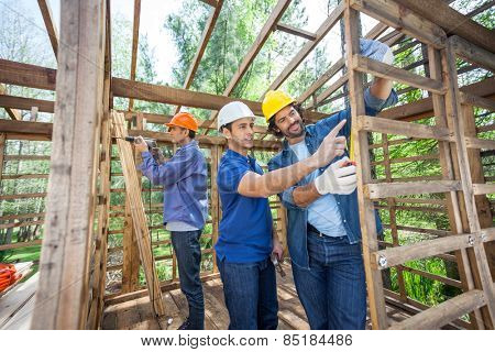 Male construction workers working in incomplete timber cabin at site