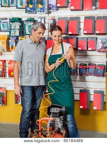 Saleswoman explaining air compressor to male customer in hardware store