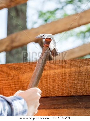 Female worker's hand hammering nail on timber frame at site