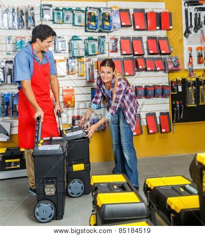 Portrait of woman selecting tool cases while salesman assisting her in hardware store