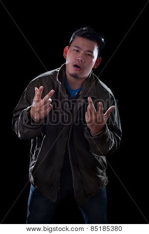 Portrait Face Of Young Asian Man Acting Like A Rocker Man Standing Against Dark Background