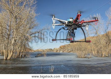 FORT COLLINS, CO, USA, March 9,  2015:  DJI F550 Flame Wheel  hexacopter drone is  flying with a camera over frozen lake.