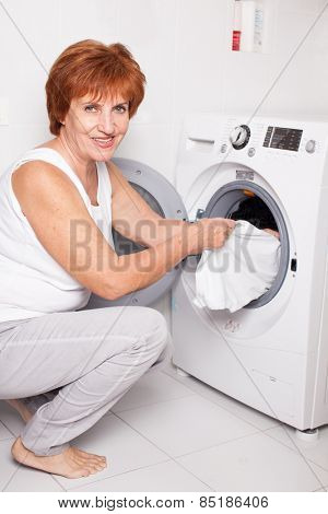 Woman puts clothes in the washing machine at home