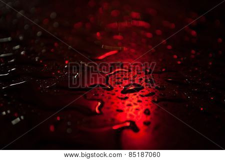 Raindrops on a table with red illumination.