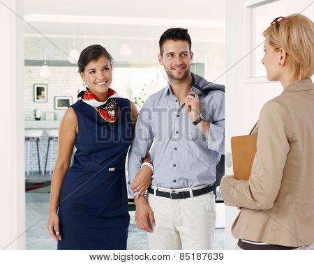 Happy caucasian formal couple meeting businesswoman at home. Smiling, standing in doorway, hand in hand, holding hands.