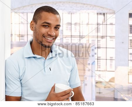 Happy casual afro american man at loft apartment home, standing, leaning against wall, cup in hand, smiling, looking at camera.